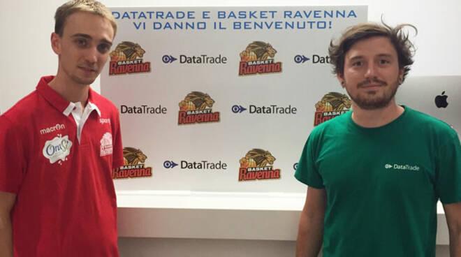 Lorenzo Ciervo dell'ufficio marketing del Basket Ravenna posa con Enrico Montanari, responsabile del punto vendita DataTrade di Ravenna, di fronte al backdrop realizzato per celebrare il rinnovo della partnership.