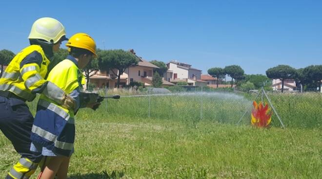 Una volontaria della Protezione Civile insegna a un bimbo come spegnere un incendio