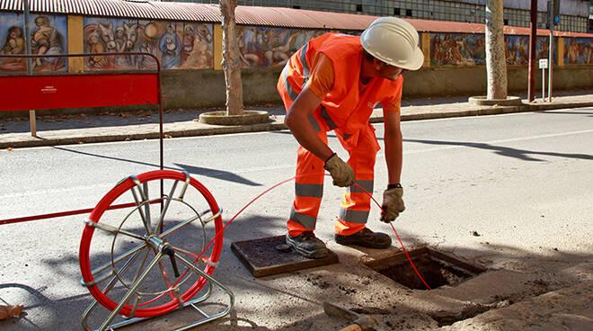 Un operaio mentre dispiega la fibra ottica